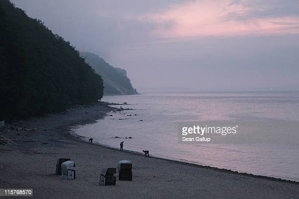 People comb a beach for souvenirs at sunset on June 7 2011 on Ruegen Island at Sellin Germany Ruegen Island located off the north German coast in the...