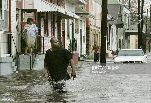 People come out of their homes to a flooded street after Hurricane Katrina hit the area with heavy wind and rain August 29 2005 in New Orleans...