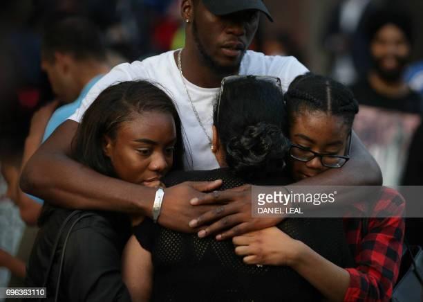 People comfort each other as they observe a vigil outside Notting hill Methodist Church following the blaze at Grenfell Tower a residential tower...