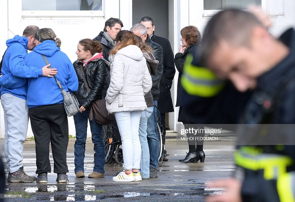 People comfort each other as they wait at the Rochefort rescue center for news about their loved ones on February 11, 2016 after at least six children were killed when a school bus crashed into a truck, police said, a day after another road accident involving a school bus left two youngsters dead. The head-on smash with a lorry carrying rubble happened at around 7:15 am (0615 GMT) in Rochefort in the Charente-Maritime region. / AFP / MEHDI FEDOUACH