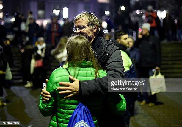 People comfort each other shortly after the match between Germany and the Netherlands was cancelled following a bomb alert at the HDIArena on...