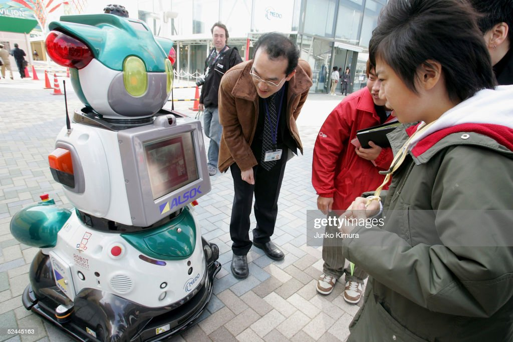 People communicate with ALSOK's security robot 'Guard Robo i' during the press day of the Aichi World Exposition 2005 on March 18 2005 in Nagakute...