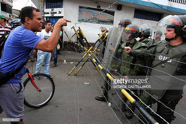 TOPSHOT People confront Bolivarian National Guard member whilst attempting to cross the Francisco de Paula Santander international bridge linking...