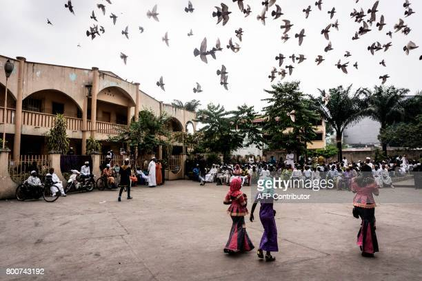 People congregate in a square before breaking the Ramadan fast as part of the Eid alFitr holiday on June 25 2017 in Kinshasa Muslims worldwide...