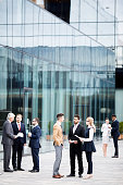 Groups of contemporary business people in formalwear standing by modern building and consulting outdoors