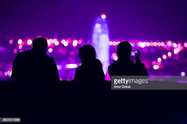 People contemplating Barcelona city at night.