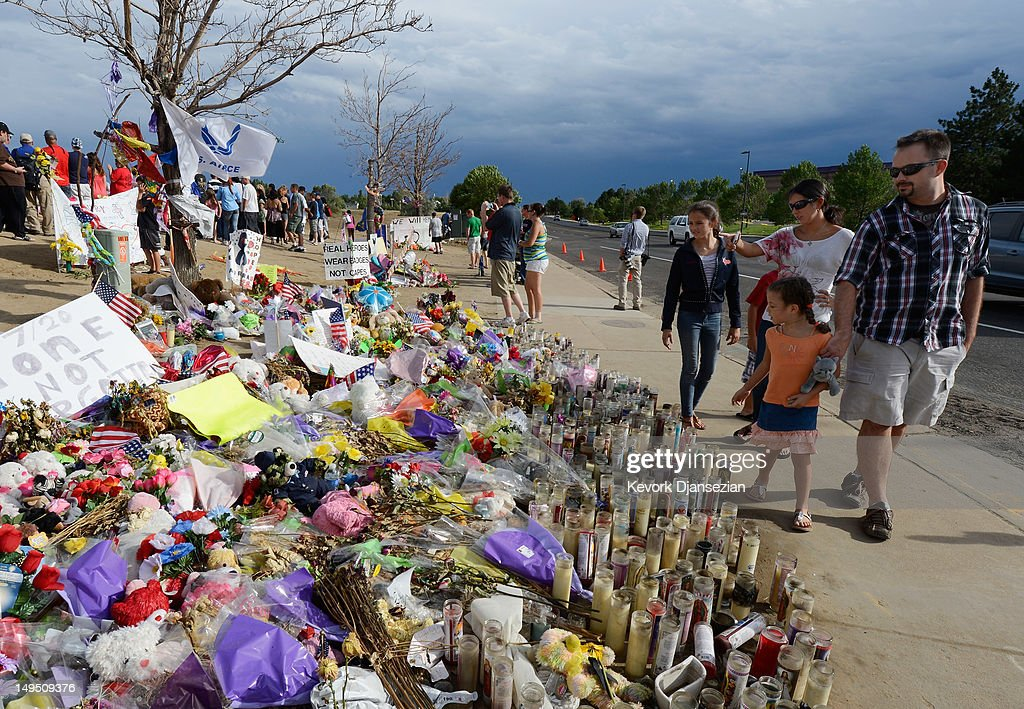 People continue to visit the roadside memorial set up for victims of the Colorado theater shooting massacre across the street from Century 16 movie theater July 29, 2012 in Aurora, Colorado. Twenty-four-year-old James Holmes is suspected of killing 12 and injuring 58 others July 20 during a shooting rampage at a screening of 'The Dark Knight Rises' in Aurora, Colorado.