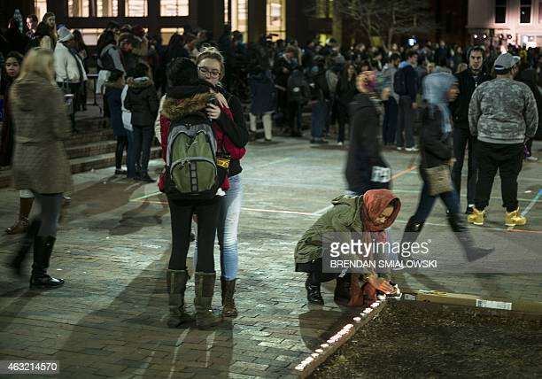 People contribute to a makeshift memorial at the close of a vigil at the University of North Carolina following the murders of three Muslim students...