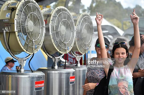People cool down in front of fans at the Sydney International tennis tournament in Sydney on January 11 2017 Sydney sweltered through scorching...