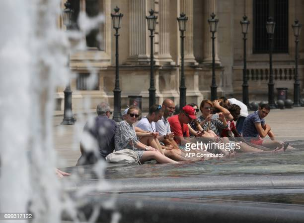 People cool off in a fountain pool near The Louvre Museum in Paris on June 21 as temperatures climb across Europe Europe continued to sizzle in a...