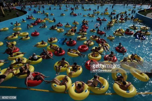 People cool off in a pool at an aqua park in Minsk on August 1 as temperatures reached 30 degrees Celsius / AFP PHOTO / Sergei GAPON