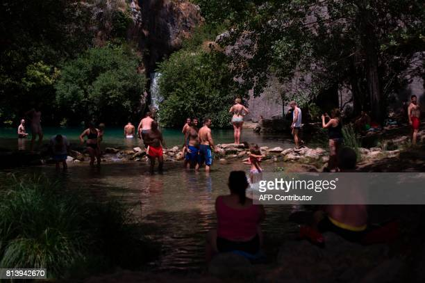 People cool off in the Guadiaro river at 'La Cueva del Gato' near Benaojan in southern Spain on July 13 2017 / AFP PHOTO / JORGE GUERRERO