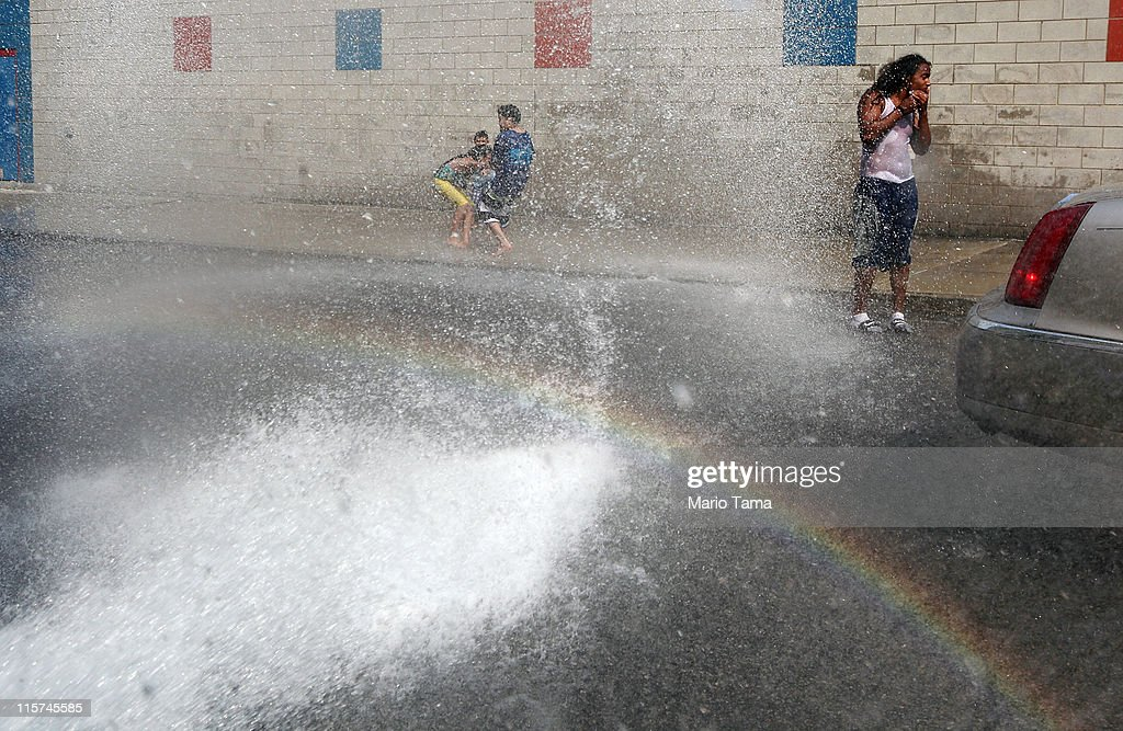 People cool off in water sprayed from a fire hydrant as a small rainbow is formed on June 9, 2011 in the Bronx borough of New York City. An early summer heat wave has hit the city with temperatures forecast to hit in the high nineties this afternoon.