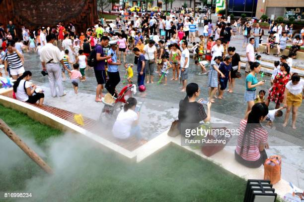 People cooloff at a watertheme square in the city on July 16 2017 in Chongqing China China entered its hottest period of the year last Wednesday the...
