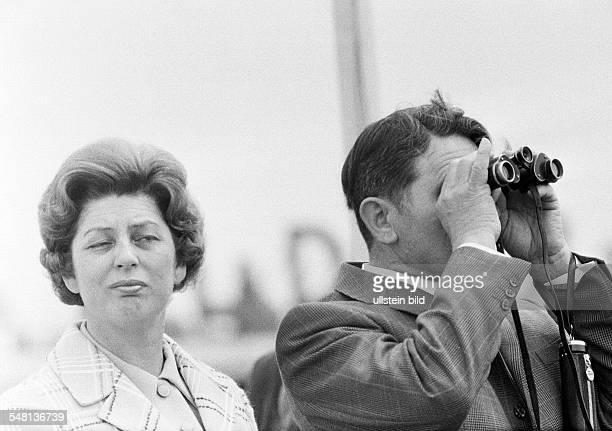 people couple freetime contrasts interest boredom man looks through a binoculars woman is bored aged 40 to 50 years