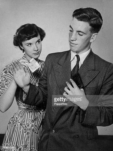 circa 1950 A young couple in a finance situation as the man puts his wallet away as the young woman takes the money