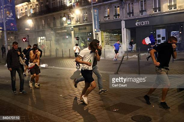 People cover their faces as they run after tear gas is fired as French riot police encounter hundreds of drunken English football fans on June 15...