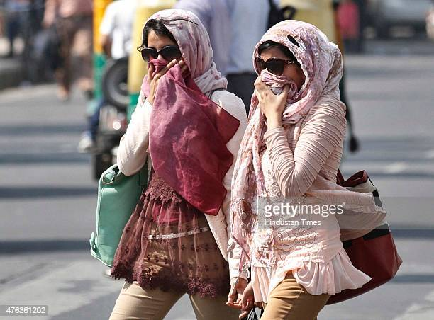 People cover themselves as protection against the heat during a hot weather as heat wave conditions prevailed in Northern India as the mercury...