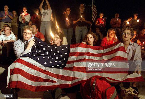 People cover themselves with an American Flag on the US Capitol grounds during a candle light vigil to remember victims who lost there life in the...
