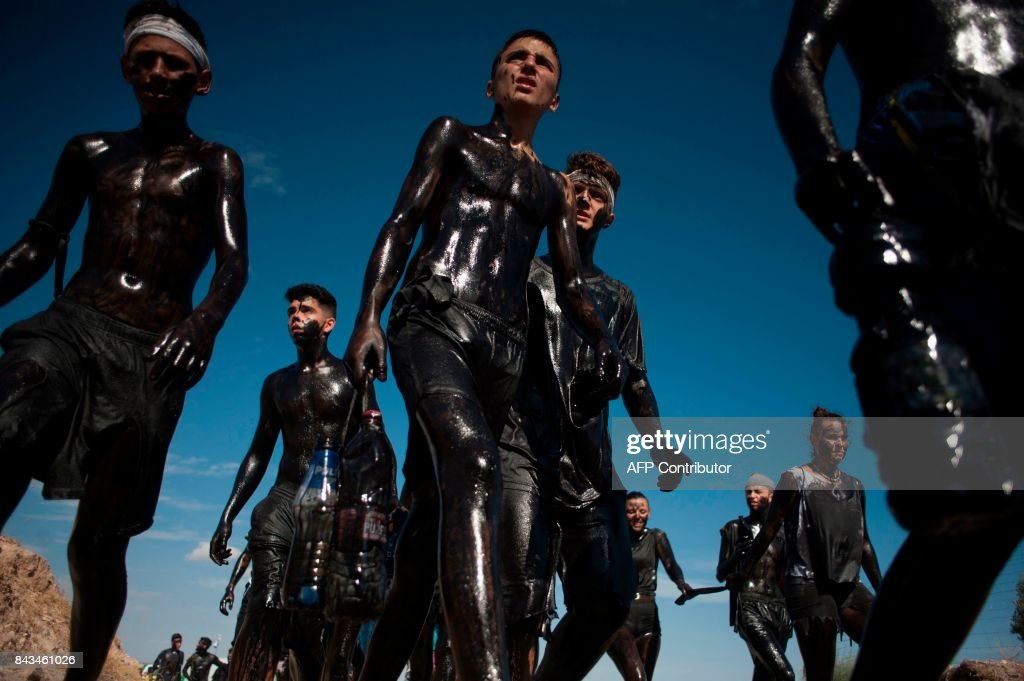 TOPSHOT - People covered in black grease walk together during the traditional festivities of the Cascamorras, in Baza, near Granada, on September 6, 2017. Every year on September 6 a villager from Guadix dresses as an oddball character called 'Cascamorras' and travels the three kilometres to the village of Baza, flanked by a team of representatives, to stage an attempt to recapture the statue of the Virgen de la Piedad before returning to Guadix after three days to be punished by the locals for his failure. /