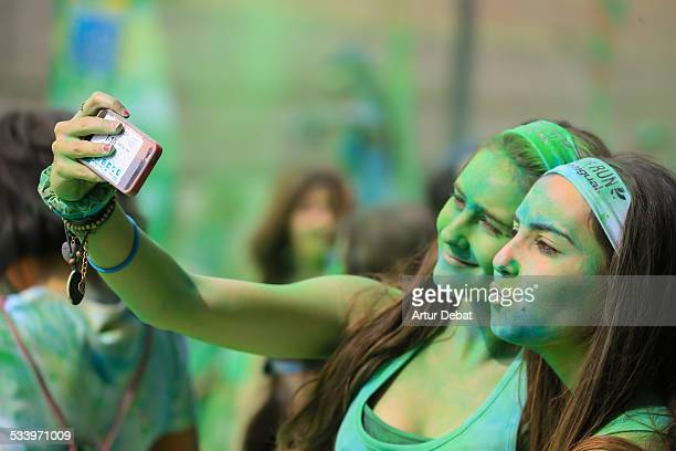 People covered with colorful Gulal powder during the Color Run a race with party music and colors in Barcelona city Catalonia Europe
