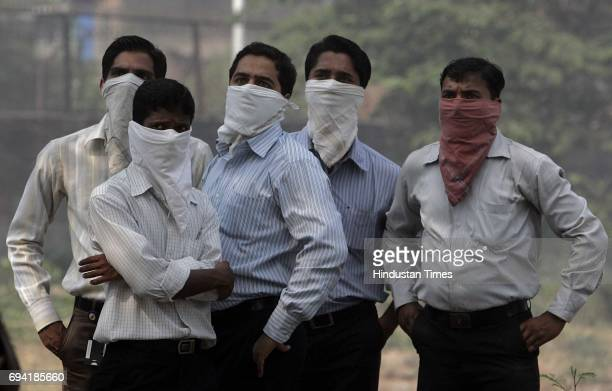 People covering their mouths with handkerchiefs to prevent themselves from inhaling the smoke emanating from fire that erupted on the third floor of...