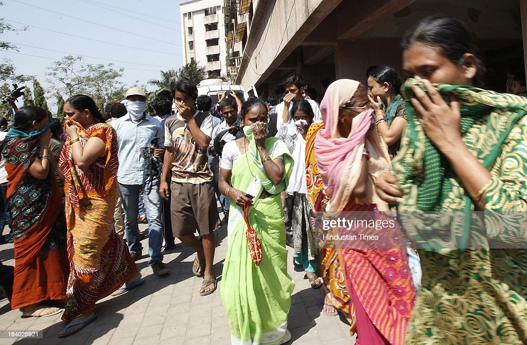 People covering their noses to evade the stink as policemen removed the four bodies found at Odyssey building in Bhakti Park, Wadala on March 18, 2013 in Mumbai, India. A couple and their two young children were found dead in their one-bedroom apartment. All the bodies had black polythene bags pulled over their faces. From the extent of decomposition, it appeared that they had been dead for at least a day and a half, police said.