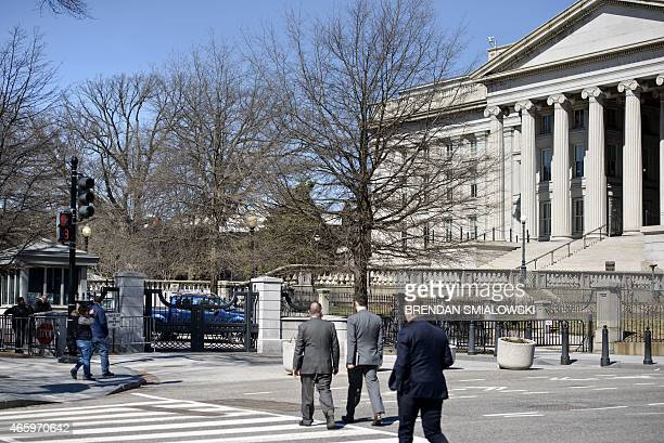 People cross 15th Street by the Treasury near a checkpoint to enter the White House grounds March 12 2015 in Washington DC AFP PHOTO/BRENDAN...