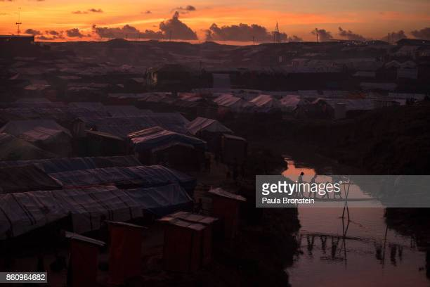 People cross a bamboo bridge over a stream as the sun sets on October 13 2017 at the Kutuplaong refugee camp Cox's Bazar Bangladesh According to UN...