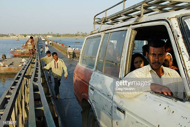 People cross a bridge over the ShatolArab River October 11 2002 in Basrah Iraq The US has dismissed Iraq's latest overtures for weapons inspections...