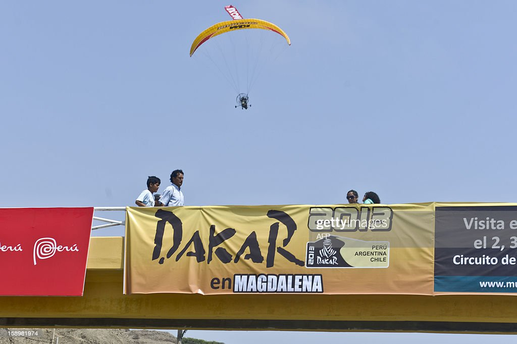 People cross a bridge with a banner advertising the 2013 Dakar Rally in Lima on January 4, 2013. This year the rally will thunder through Peru, Argentina and Chile from January 5 to 20.