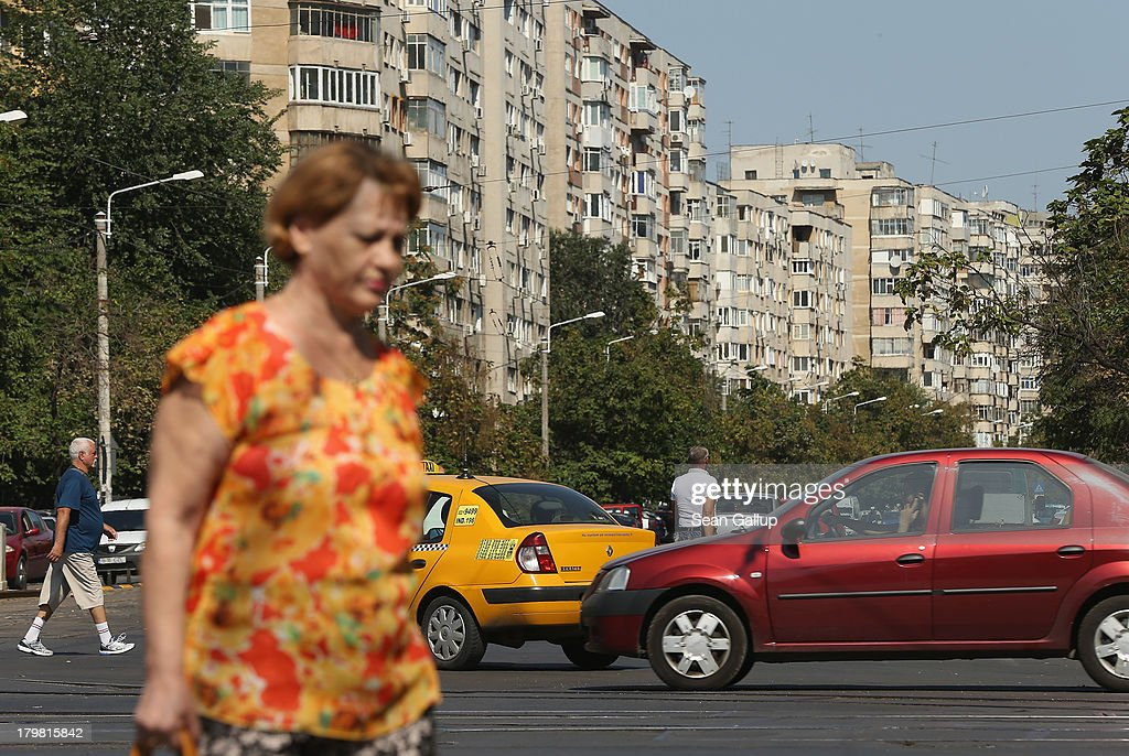 People cross a busy street as communist-era apartment buildings loom behind in Titan district on September 7, 2013 in Bucharest, Romania. While Romania's economic output has risen significantly since it joined the European Union in 2007, it still lags in infrastructure development and the fight against corruption.