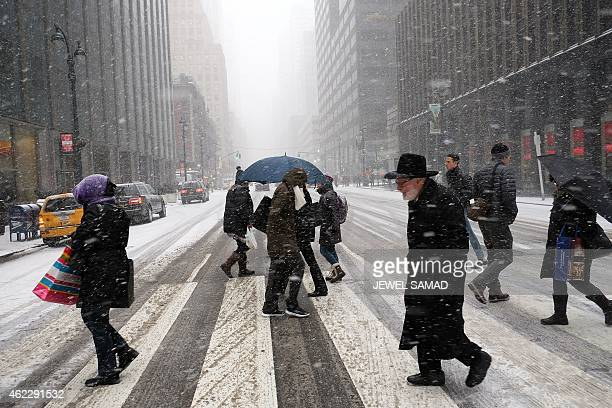 People cross a city street in a snow storm in New York on January 26 2015 Thousands of flights were canceled Monday as millions of Americans in the...