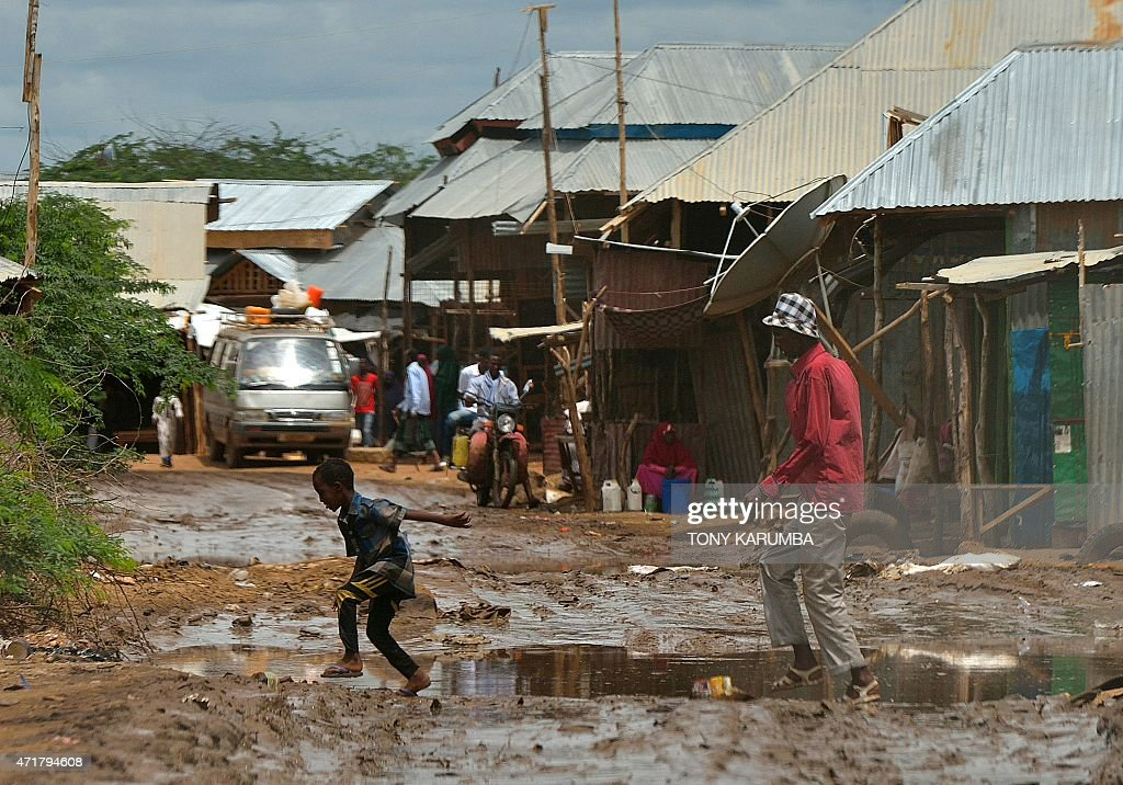 People cross a muddy street at the market at IFO main camp of the Dadaab refugee camp north of the Kenyan capital Nairobi on April 28 2015 AFP...