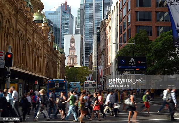 People cross a road during a busy morning hours to reach their offices in central business district of Sydney on March 6 2013 Australia's central...