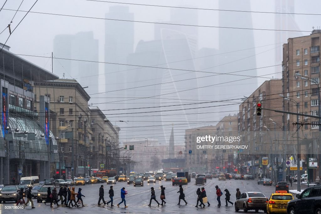 People cross a road in central Moscow, with the buildings of the Moscow International Business Center (Moskva City) seen in the background, on February 12, 2016. AFP PHOTO / DMITRY SEREBRYAKOV / AFP / DMITRY SEREBRYAKOV