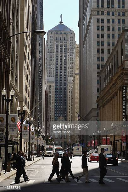 People cross a street as the Chicago Board of Trade Building sits at the south end of LaSalle Street in the Chicago Loop's financial district on...