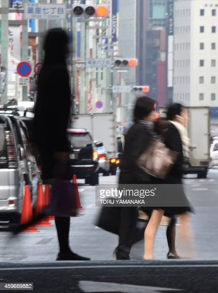 People cross a street at a shopping and business district in Tokyo on November 28 2014 Japan released a string of lacklustre economic data Friday...