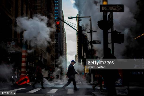 People cross a street emitting smoke in New York on November 15 2017 PHOTO / Jewel SAMAD