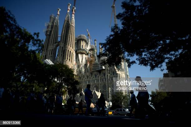 People cross a street near the 'Sagrada Familia' basilica in Barcelona on Ocotober 13 2017 Spain's government said today it could lower its forecast...