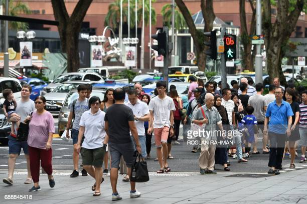 People cross a traffic junction in the Orchard Road shopping district in Singapore on May 27 2017 / AFP PHOTO / Roslan RAHMAN