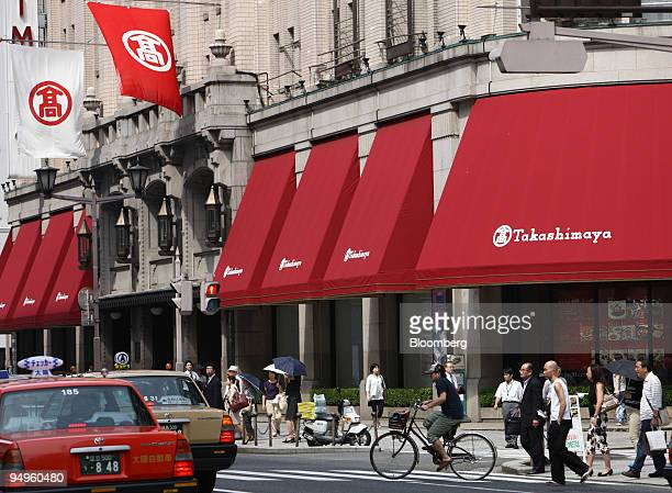 People cross an intersection in front of a Takashimaya department store in the Nihonbashi district of Tokyo Japan on Friday June 26 2009 Japan's...