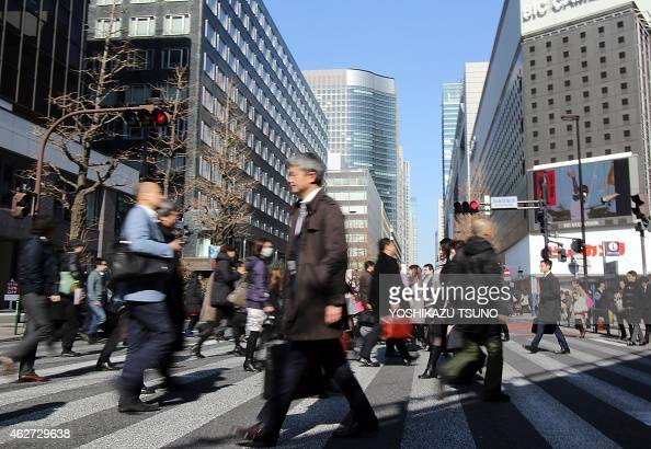 People cross an intersection in Tokyo on February 4 2015 Japan is considering making it compulsory for workers to take at least five days' paid...
