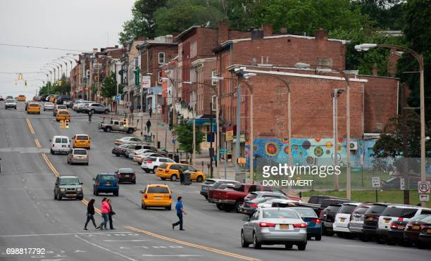 People cross Broadway in traffic on May 30 in Newburgh New York Rows of boardedup homes became a ubiquitous symbol of the US housing crash Some 10...