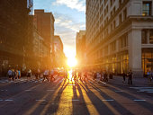 People cross busy intersection on 23rd Street in Manhattan New York City with the colorful light of sunset casting long shadows