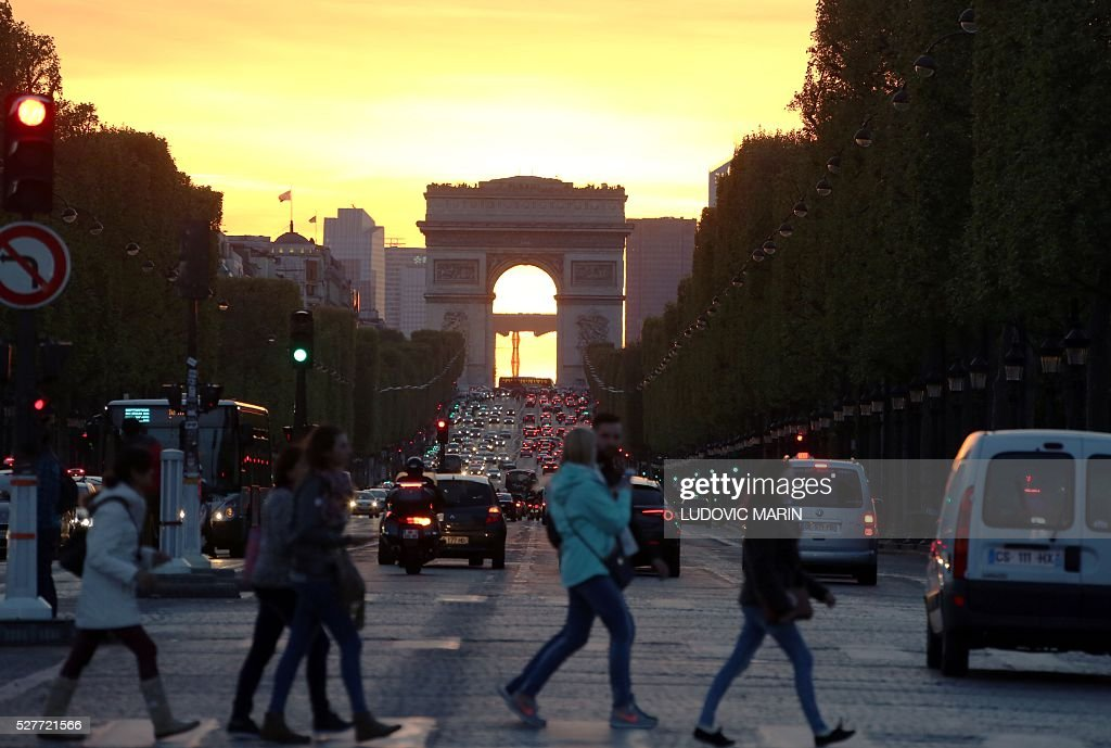 People cross Champs Elysees Avenue in Paris at sunset on May 3, 2016. / AFP / LUDOVIC