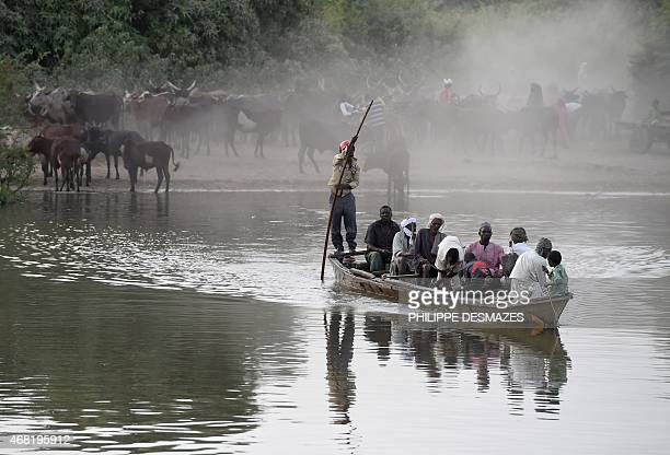 People cross in a boat a section of Lake Chad whose waters border Niger Nigeria and Cameroon on March 30 2015 at the village of Guite in Chad's lake...