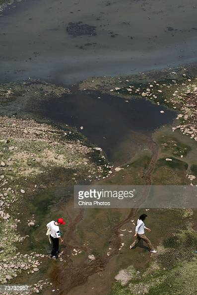 People cross polluted water from the Yangtze River March 28 2007 in Chongqing Municipality China China is to begin an allout effort to protect its...