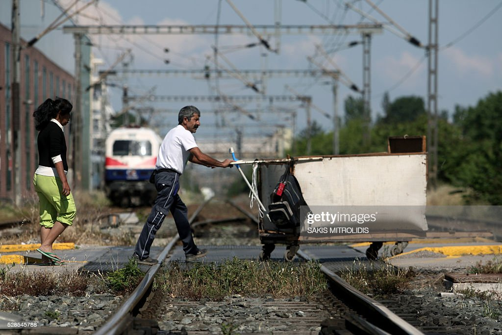 People cross railway tracks during a 48-hours public transport strike in Thessaloniki on 6 May, 2016. Greece's labour unions stage a two-day general strike to protest against controversial government plans to overhaul pensions and increase taxes to meet demands of its bailout creditors. / AFP / SAKIS