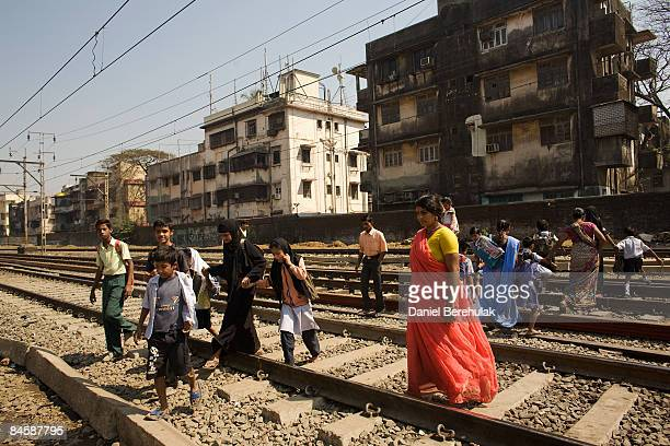 People cross railway tracks in the Dharavi slum on February 2 2009 in Mumbai India The redevelopment of asia's largest slum the Dharavi spanning over...